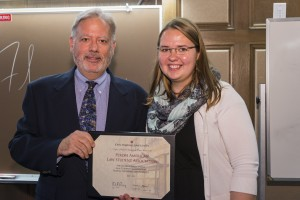 Associate Dean William Powers presents the Polish-American Students Association President Magdalena Wilk with the honorable mention for the group's outstanding programs.