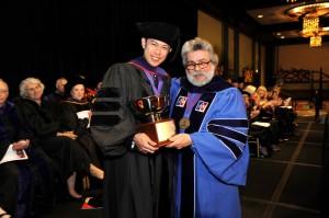 Professor Daryl Lim (left) accepts congratulates from Associate Dean Ralph Ruebner on receiving the Faculty Scholarship Award.